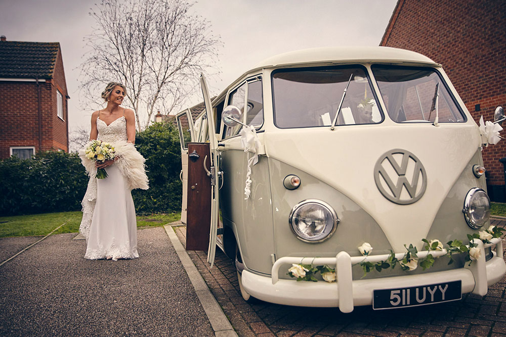 Bride stands next to a white and green split screen camper