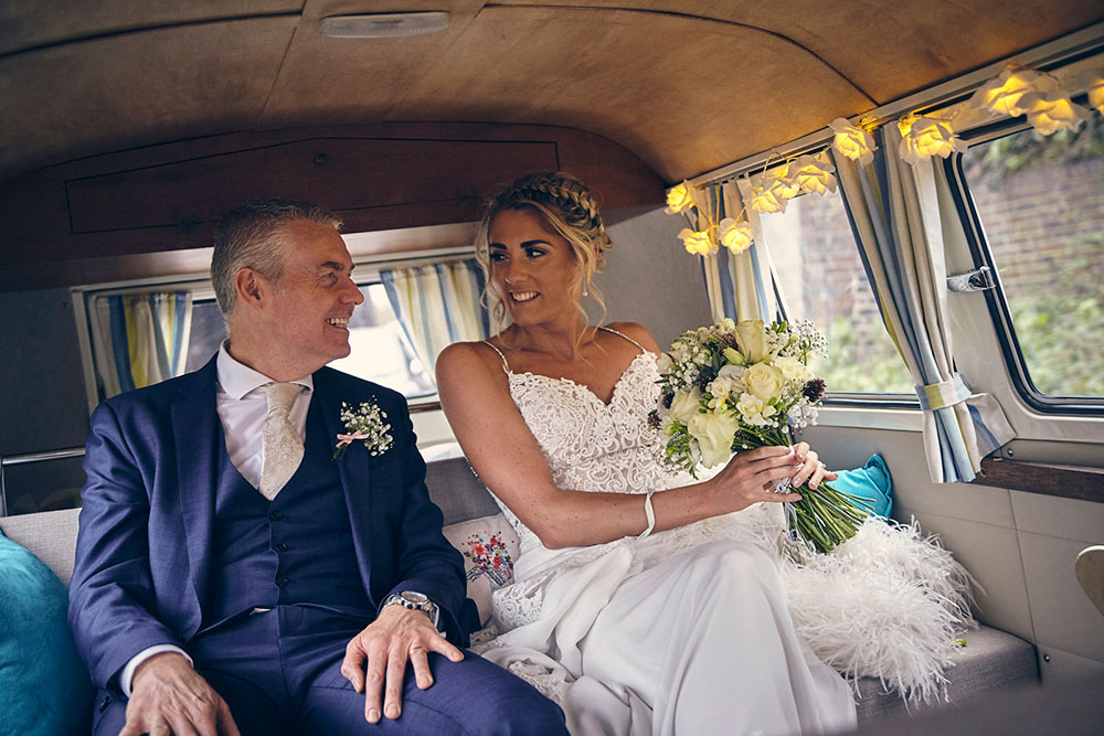 Bride and her father in the back of a vintage VW campervan on the way to the wedding