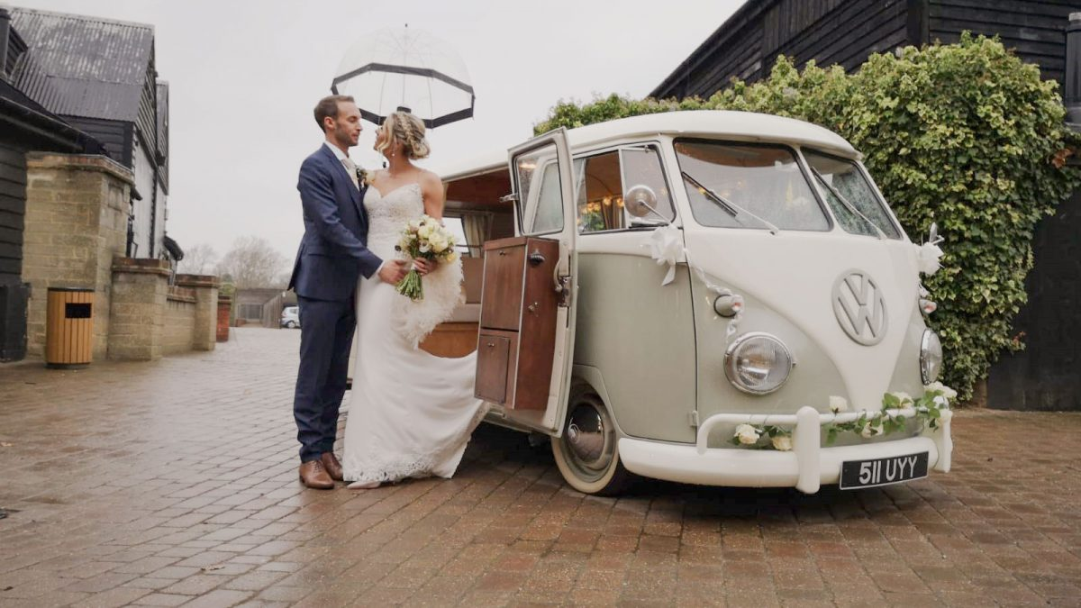 bride and groom standing next to VW split screen camper on their wedding day