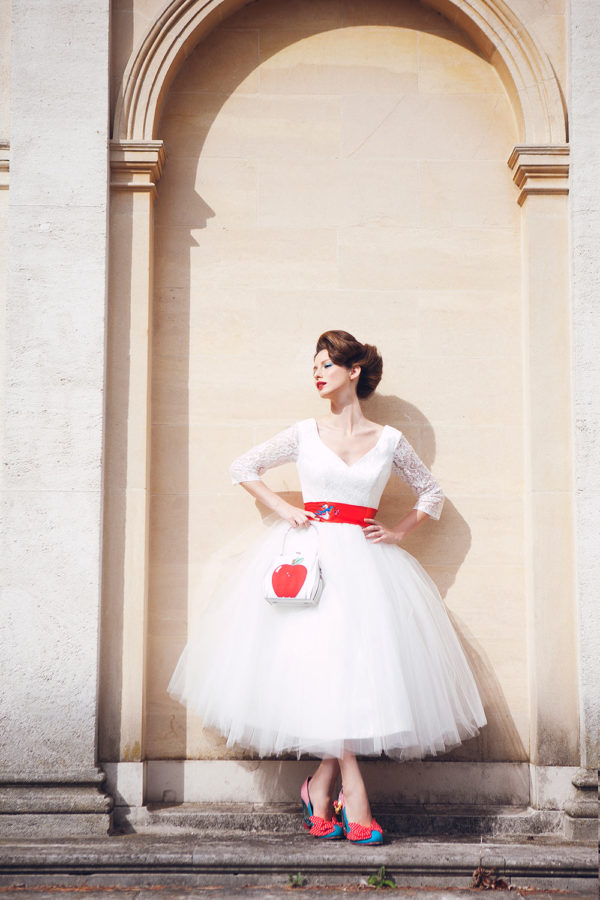 Tea length, ivory lace and tulle gown with red satin sash tied around waist