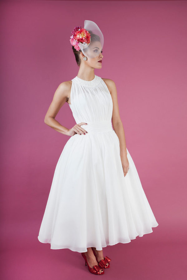 Tea-length bridal gown with sequin and beaded neckline and pleated ivory chiffon.